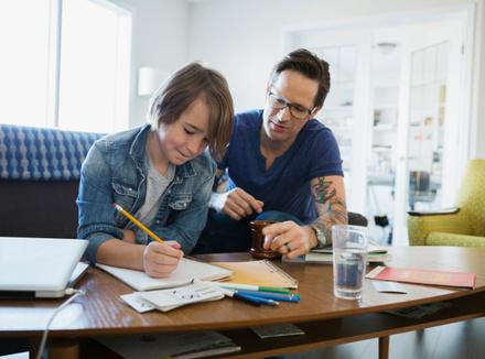 Отец помогает ребенку делать уроки