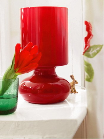Маленькая настольная лампа из выдувного стекла (IKEA) будет заливать комнату теплым красноватым светом. Люстра из акрила и стекла (Kare Design, Германия) – один из ярких акцентов в интерьере
