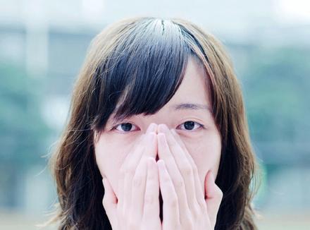 Женщина, закрывающая рот руками