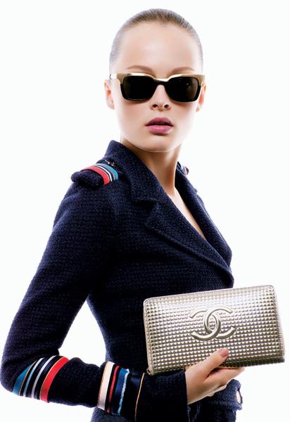 Сливки общества: очки в металлической оправе; стеганый клатч из металлизированной кожи с логотипом; пиджак с поясом из твида и шерсти, декорированный шелковыми лентами, все – Chanel.