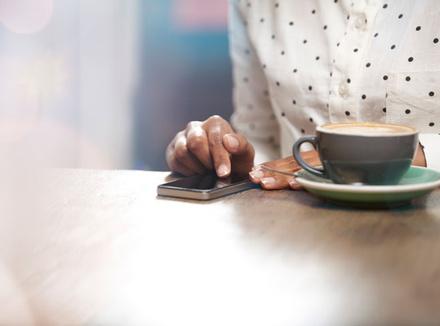 Женщина с чашкой кофе и телефоном