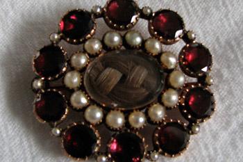 Брошь из драгоценных камней, в центре которой плетеная композиция из волос.
