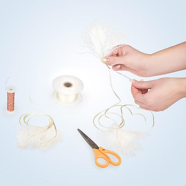 Разрезаем пластиковую ленту на две одинаковые полоски длиной примерно 50-60 см. К концам ленты при помощи проволоки прикрепляем кусочки перышек — очаровательные, пушистые кончики.