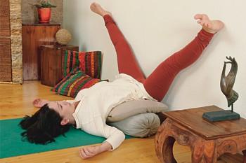 2. Через две минуты широко разведите ноги, как в позе Упавишта конасана. Носки стоп тяните на себя, следите за тем, чтобы задняя поверхность ног плотно прижималась к стене.