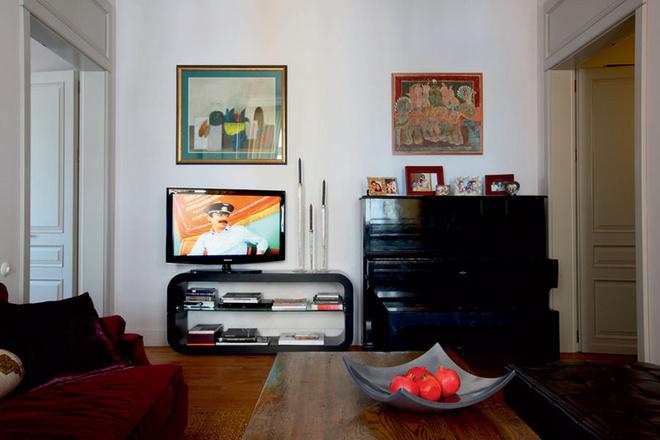 Гостиная объединена с кухней, плита, Ascot. Низкий стол– одновременно журнальный и обеденный. Над пианино «Енисей» висит работа Ираклия Сутидзе.