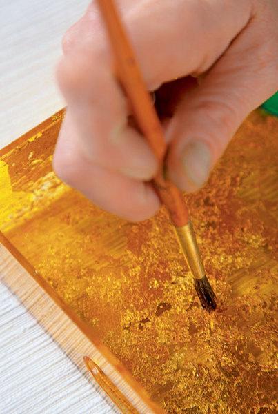 Затем к подносу приклеивают лист сусального золота. Спомощью кисти золото «разбивают» нанебольшие фрагменты, создавая эффект патины. Полученную поверхность тонируют желтой краской. Работа завершена.