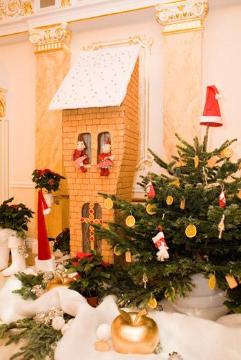 Съедобный дом и елка, украшенная сладкими шишками, гигантскими карамельными палочками, фруктами, мармеладом.