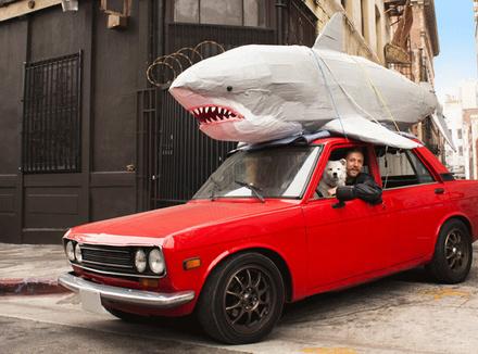 Человек в красной машиной с акулой на крыше