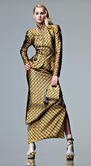 1997 Кол-лекция Prêt-à-Porter осень—зима. Джон Гальяно для Dior Жакет в китайском стиле с воротником-стойкой, расшитым жемчугом, проймой кимоно и прямыми узкими рукавами из жаккардовой ткани imperial, длинная юбка с асимметричной складкой, сумочка с позолоченными ручками, туфли и сандалии на платформе.