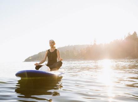 Женщина медитирует в лодке
