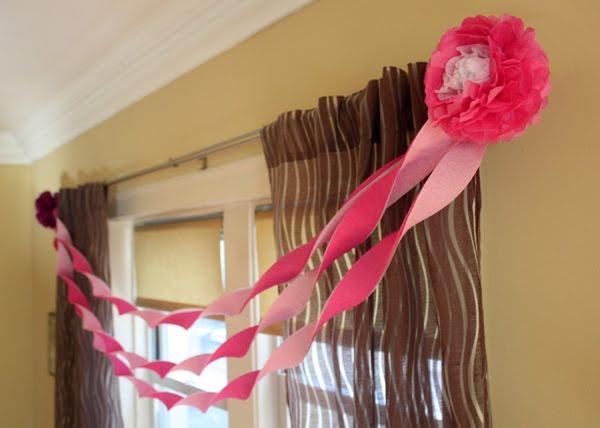 Праздничная гирлянда на окно: гофрированные цветы прикрепляются к шторам и соединяются лентами.