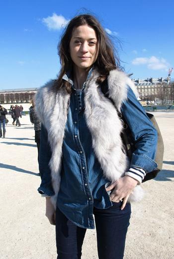 Меховые жилеты приходят на смену теплым зимним шубкам. Короткий серый мех красиво сочетается с джинсами и рубашкой, которая надета поверх тельняшки с длинными рукавами.