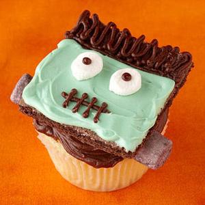 Франкенштейн. Квадратное печенье превратить в страшное лицо с помощью крема и шоколада и водрузить сверху на кекс.