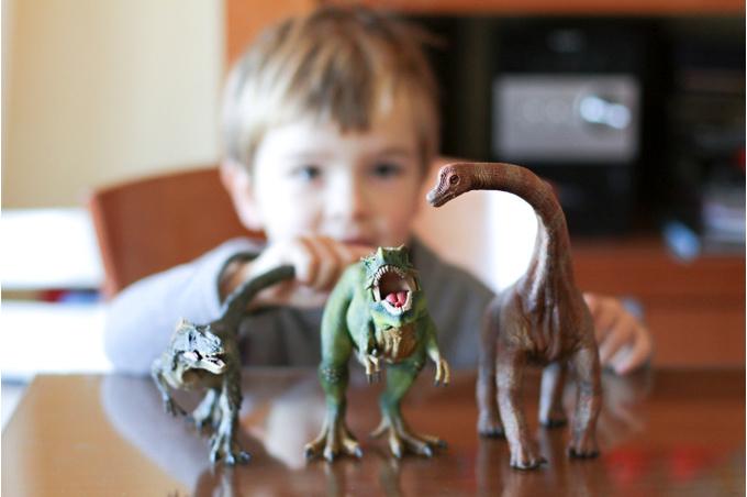 Мальчик играет с динозаврами