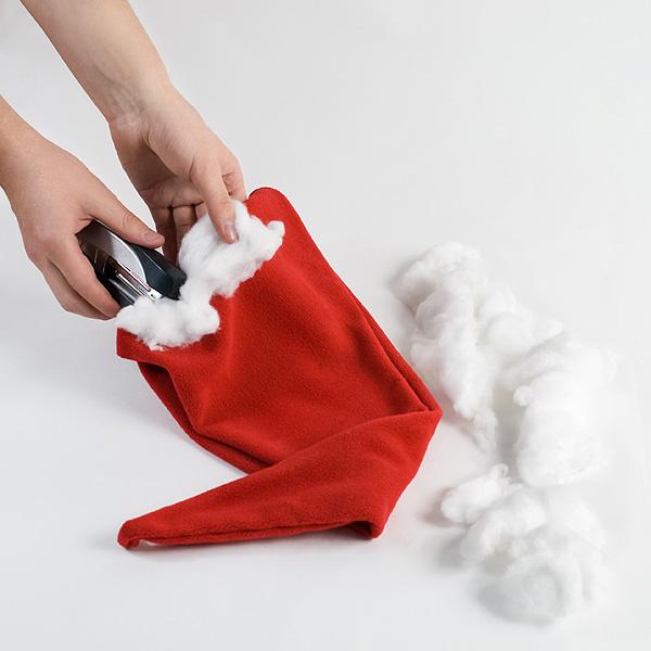 Шаг 2. Разве может быть колпак Санта-Клауса без роскошной белой каймы? С помощью все того же степлера прикрепляем к краям колпака вату.