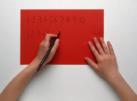 Человек пишет левой рукой цифры
