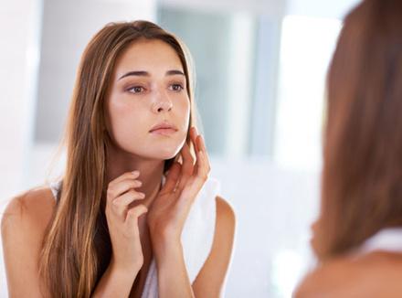 Девушка смотрит на себя в зеркало