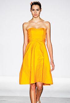 Платье с открытыми плечами насыщенного шафранового цвета.