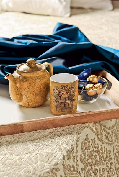 Для хранения постельных принадлежностей служит узкий и длинный сундук, помещенный в изножье кровати. Заметим, что гармонично вписать в интерьер этот современный постилистике предмет помогло покрывало, затканное медальонами.