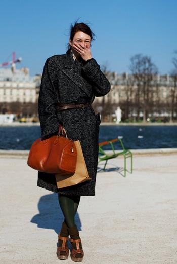 Да, в России крайне редко можно встретить девушку, надевающую босоножки на гольфы, при этом закутанную в теплое пальто. Сочетать вещи не просто из разных стилей, но из разных сезонов – отличительная особенность европейских модников. Яркий акцент ее образа – чулки болотного цвета и бурая сумка.