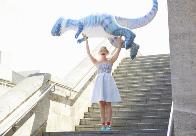 Девушка держит на руках динозавра