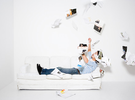 Мужчина подкидает страницы журнала