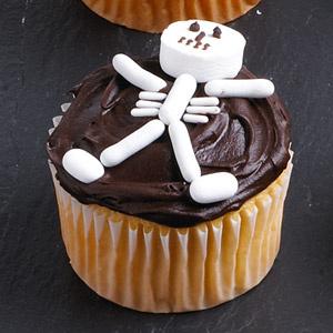 Жертва. Намазать кекс шоколадной пастой и выложить сверху человечка из мятных леденцов tic-tаk и жевательных конфет.