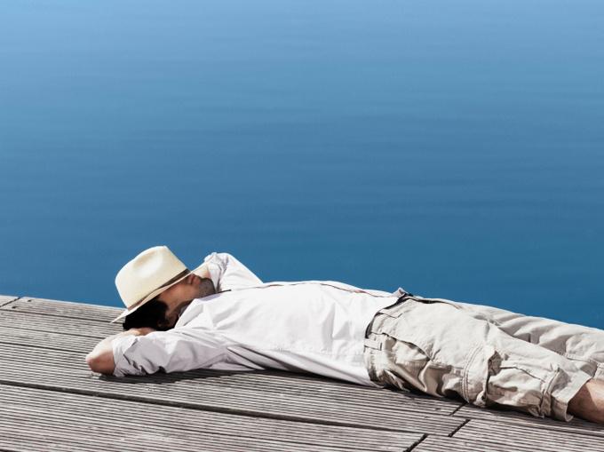 Юноша лежит на деревянных мостках