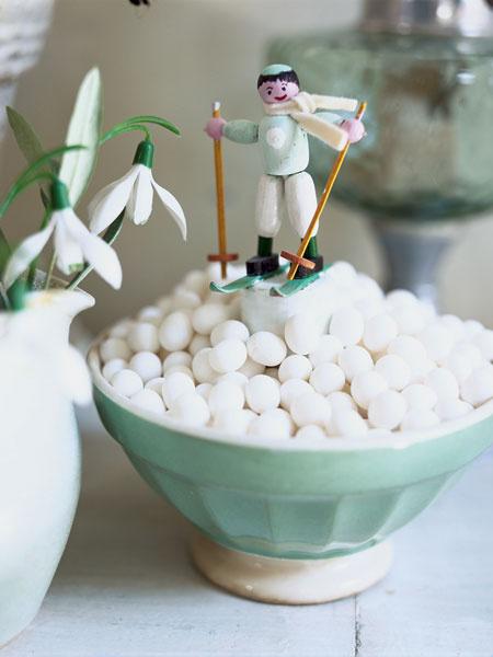 Мятные конфеты, насыпанные горкой в керамическую чашу, напоминают высокий сугроб. Вниз по склону мчится игрушечный лыжник.
