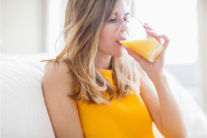 Женщина пьет апельсиновый сок