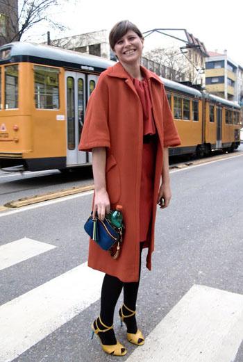 Бурый, охристый, терракотовый – оттенки красного кирпича – в фаворе у парижанок. Эта девушка смело надевает широкое прямое пальто с темными чулками и ярко-желтыми босоножками. Менее экстравагантно можно выглядеть, если подобрать ботильоны в тон к чулкам.