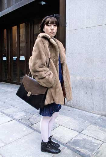 Белые чулки, винтажный портфель, светло-бежевая широкая шуба и оригинальный головной убор – каждый предмет одежды девушки привлекает к себе внимание, при этом не выбивается из образа.
