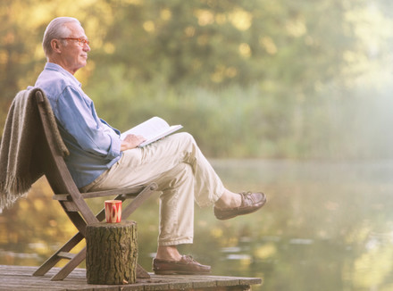 Мужчина в возрасте с книгой на коленях