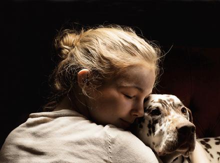 Девушка, обнимающая свою собаку