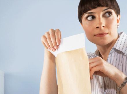 Женщина, заглядывающая в конверт