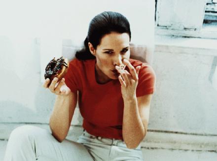 Женщина ест пончик с шоколадом