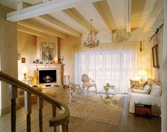 Гостиная имеет выход на террасу. Столик от Minimax окружают стулья, Smania. Зеркало - от Chelini. Портал камина выполнен из травертина.