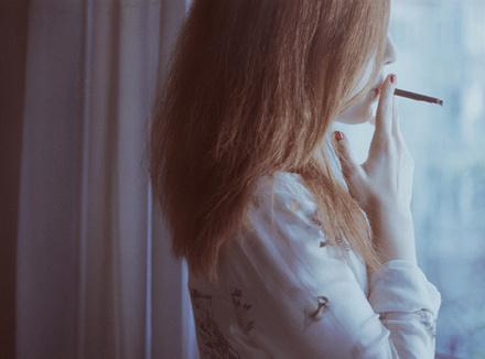 Женщина курит у окна