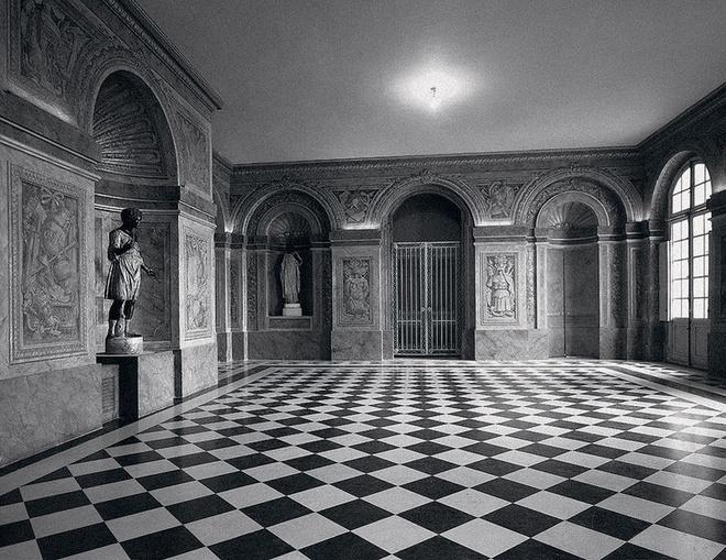 Один из залов Версальского дворца Ambassadors' Salon, на стенах роспись трамплей (обманка), изображающая доспехи и оружие. Пол из черно-белого мрамора (XVIII век).