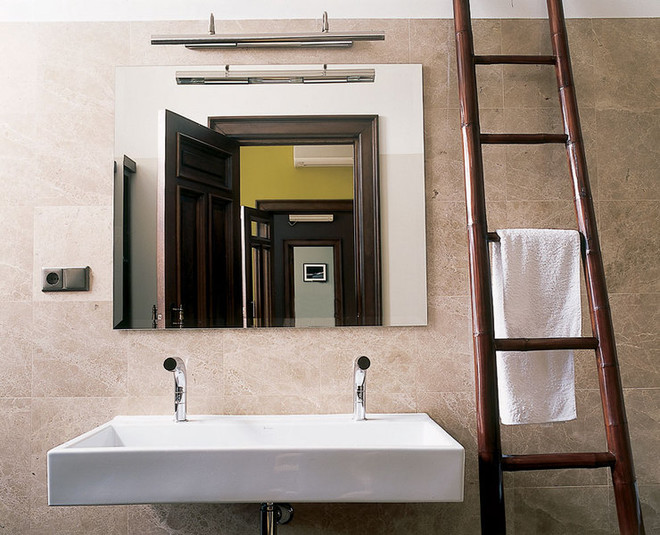 Анфиладу комнат замыкает ванная. В зеркале отражается практически все пространство квартиры.