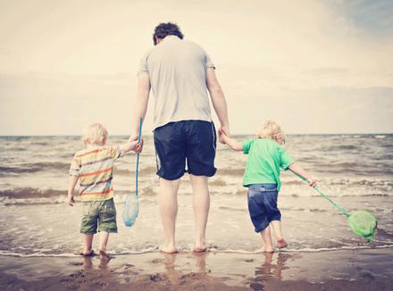 Отец с двумя мальчиками на берегу моря