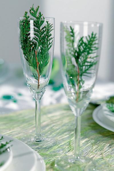 Идея №13. Мини-вазы. Если поставить на стол чуть больше прозрачных бокалов, полученный излишек можно использовать как вазы. Например, фужеры для красного вина подойдут для соснового лапника, а бокалы для шампанского – для веточек туи.