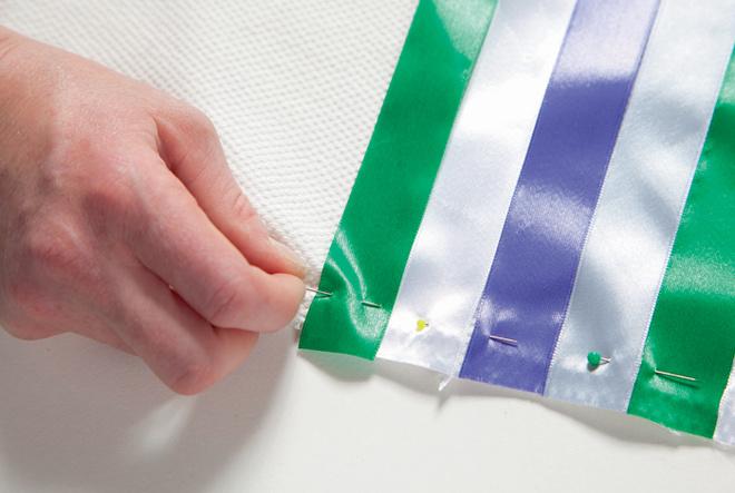 Чередуя атласные ленты по цвету, спомощью булавок их прикрепляют кобеим половинкам чехла, после чего приметывают и прострачивают
