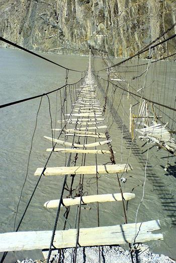 Раскачивающаяся над бурлящим рекой Хунзой хлипкая конструкция до сих пор используется местными жителями по назначению. По нему переправляются даже женщины!