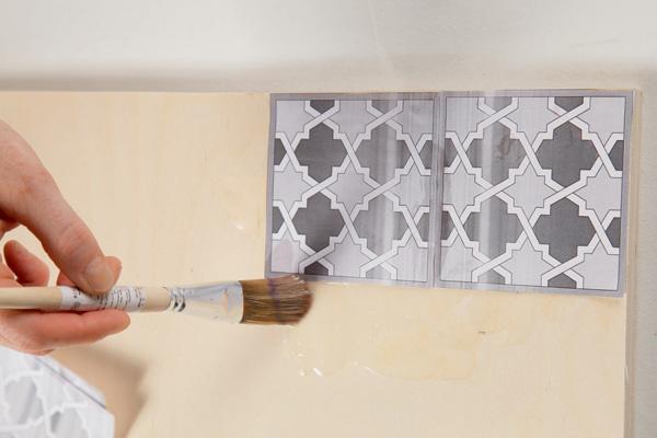 Распечатки совмещают с двумя листами фанеры (40 × 40 см) и раскрашивают желтой и фиолетовой красками, создавая мозаичный узор.