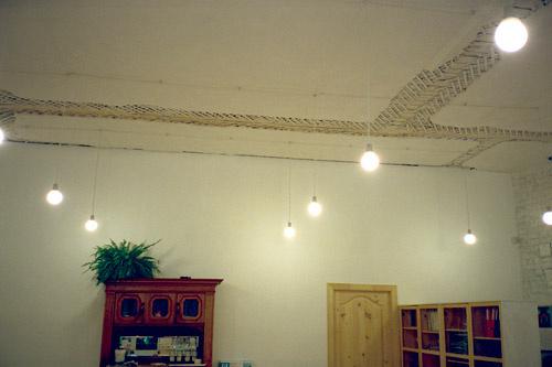 Высокие потолки украшает множество электрических лампочек, висящих на длинных проводах.