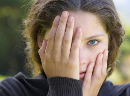 Девушка закрывает руками лицо