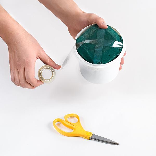 Шаг 3. С помощью клейкой ленты закрепляем намоченный пиафлор в ведерке из-под майонеза. В пиафлор мы будем вставлять различные элементы украшения нашей композиции.