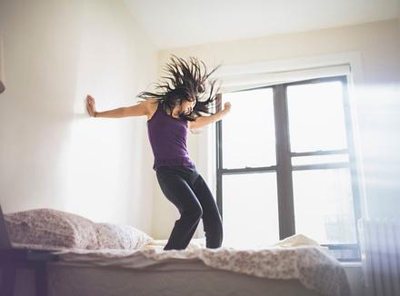 Женщина танцует в постели