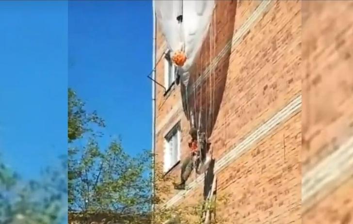 Фото №1 - Вэдэвэшник в Приморье при высадке зацепился парашютом за жилой дом и повис. Операцию по его спасению сняли на видео